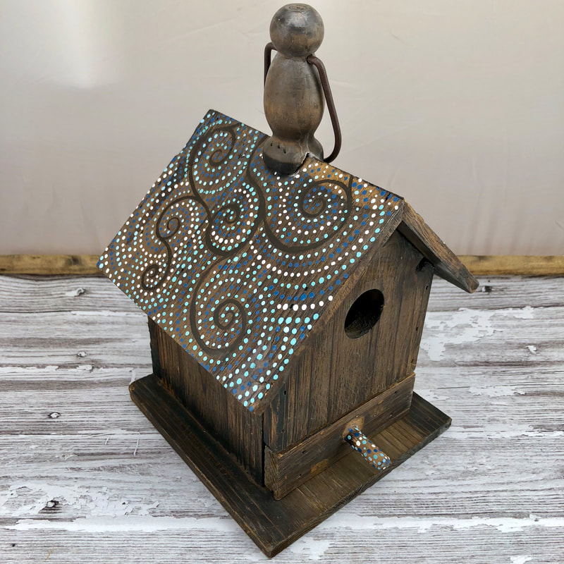 dot art painting on a bird house