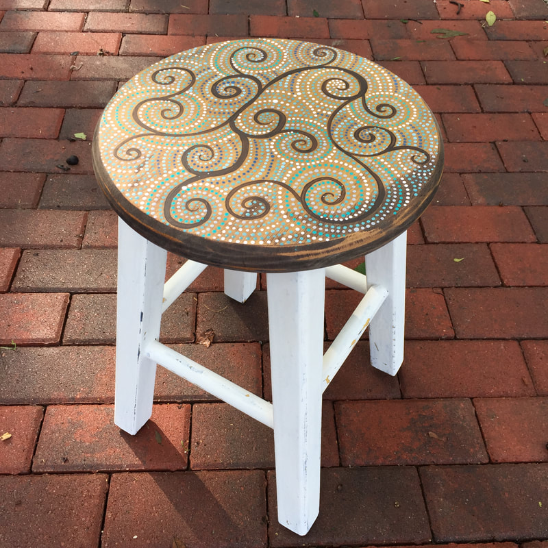 dot art painting on a wood stool